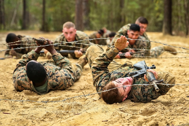 Marines crawl under a barbed wire obstacle during a combat endurance course.