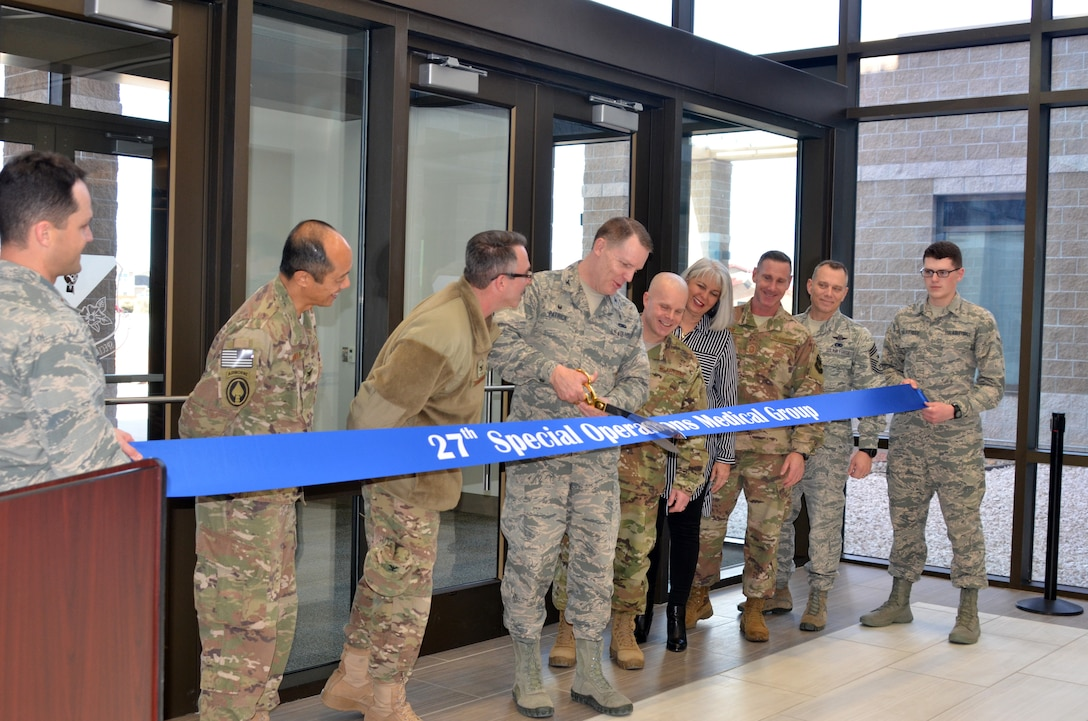 Col. Christopher Patrick, Commander, 27th Special Operations Medical Group, prepares to cut the ribbon officially opening the new medical/dental clinic, Feb. 23, 2018.