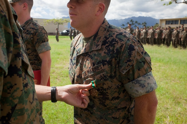 Lance Cpl. Jacob Baker, a cryptologic linguist with 3rd Radio Battalion (3rd RADBN), is awarded the Navy and Marine Corps Achievement Medal by Lt. Col. William Osborne, the commanding officer of 3rd RADBN, Marine Corps Base Hawaii, Feb. 16, 2018. Three Marines, including Baker, conducted a late night search and rescue for a lost hiker back in January 2018. The Marines covered 10 miles at about 3000 feet in elevation under rainy conditions, eventually finding and returning back with the hiker. (U.S. Marine Corps photo by Sgt. Jesus Sepulveda Torres)
