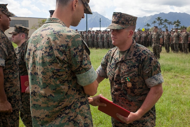 Lance Cpl. Jacob Baker, a cryptologic linguist with 3rd Radio Battalion (3rd RADBN), is presented a Navy Marine Corps Achievement Medal by Lt. Col. William Osborne, the 3rd RADBN commanding officer, Marine Corps Base Hawaii, Feb. 16, 2018. Three Marines, including Baker, conducted a late night search and rescue for a lost hiker back in January 2018. The Marines covered 10 miles up about 3000 feet in elevation under rainy conditions, eventually finding and returning back with the hiker. (U.S. Marine Corps photo by Sgt. Jesus Sepulveda Torres)