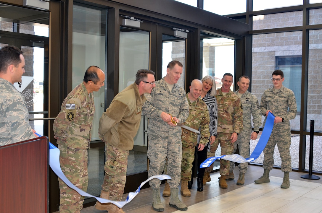 Col. Christopher Patrick, Commander, 27th Special Operations Medical Group, cuts the ribbon officially opening the new medical/dental clinic, Feb. 23, 2018.