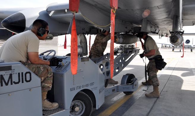 Tech. Sgt. Nathan Wesley, and Airmen 1st Class Rey Nino Estrella and Carlito Yalon, weapons loader Airmen assigned to the 303rd Expeditionary Fighter Squadron, load a 500 pound GPS-guided bomb on an A-10 Thunderbolt II before a mission at Kandahar Airfield, Afghanistan Feb. 10, 2018.