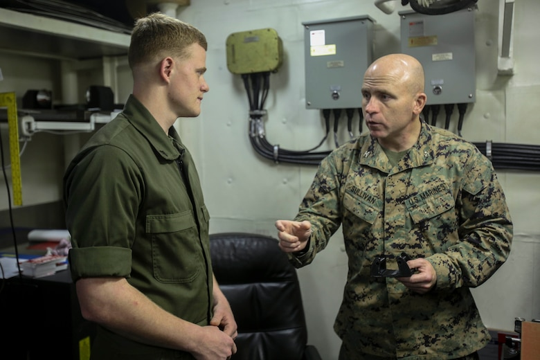 Col. Farrell J. Sullivan, commanding officer of the 26th Marine Expeditionary Unit, asks Cpl. Christopher Bigham, a machinist with the Combat Logistics Battalion 26, 26th Marine Expeditionary Unit a question about the 3D printer aboard the amphibious assault ship USS Iwo Jima (LHD 7) in the Atlantic Ocean, Feb. 26, 2018.