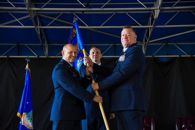 Col. Kurt Matthews (left), 920th Rescue Wing Commander, hands Col. Leo J. Kamphaus, Jr. (right) the 920th Maintenance Group guidon, officially recognizing Kamphaus' assumption of command over the maintenance group. The ceremony is a common staple in military units around the world. (U.S. Air Force photo by Senior Airman Brandon Kalloo Sanes)