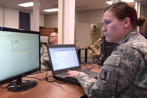 A soldier works at her computer.