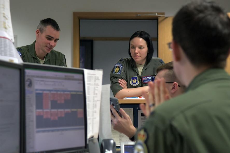 "U.S. Air Force Capt. Raychel Bates, center, 351st Air Refueling Squadron assistant ""A"" flight commander, discusses the process of building aircrews for the exercise on RAF Mildenhall, England, Feb. 26, 2018. Aircrews are comprised of two pilots and a boom operator, who conducts the refueling. (U.S. Air Force photo by Airman 1st Class Benjamin Cooper)"