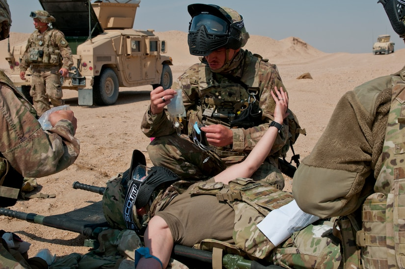Sergeant Natasia White, a truck driver and simulated casualty, reaches to an Army combat lifesaver-trained Soldier for support as another Soldier prepares to give her a saline lock during training on Gerber Training Area, Udairi Range Complex, Kuwait, Feb. 26, 2018. The exercise culminated in a simulated medical evacuation with a UH-60 Black Hawk air ambulance and also featured an IED lane and opposing forces role players.