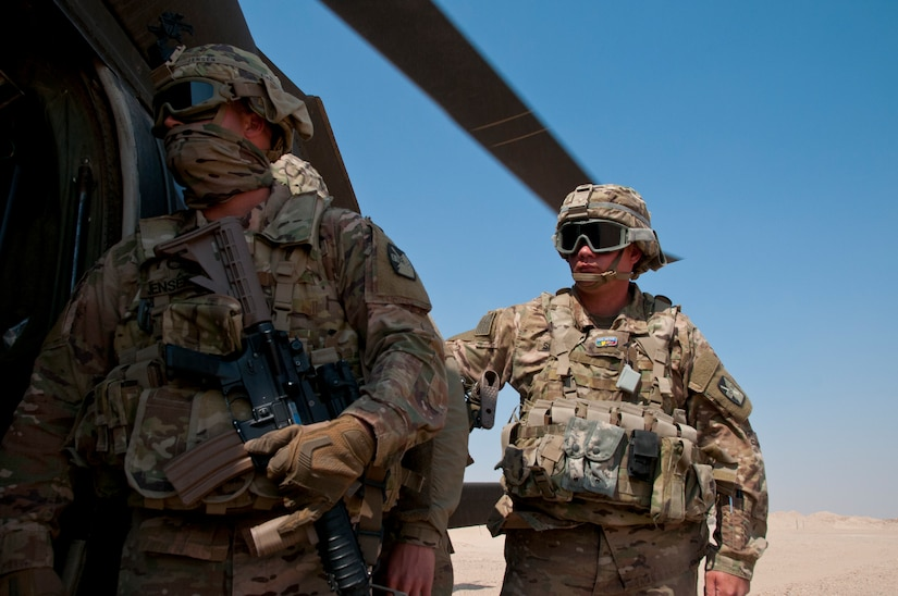 Noncommissioned officers with Delta Battery, 1st Battalion, 145th Field Artillery Regiment, Utah National Guard, watch a UH-60 Black Hawk air ambulance crew load simulated casualties into the helicopter during training on Gerber Training Area, Udairi Range Complex, Kuwait, Feb. 26, 2018. The exercise included an IED lane and enemy fire in a hostile village before culminating in the simulated medical evacuation.
