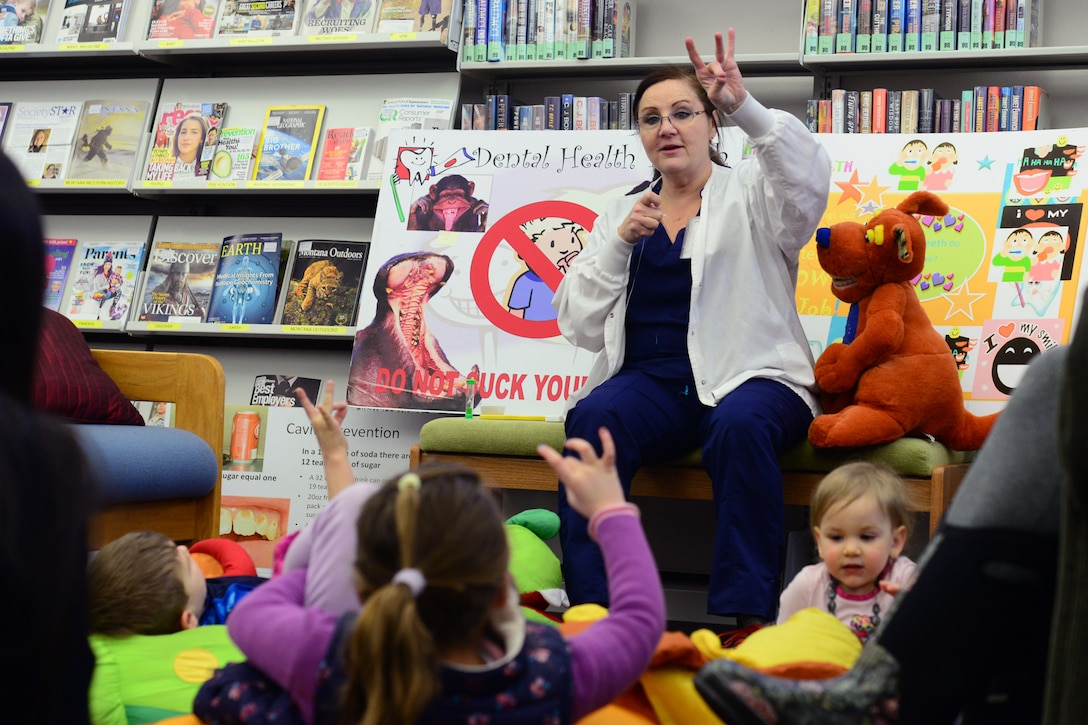 Mercy Padgett, 341st Medical Operations Squadron chief of preventative dentistry, shows children how to properly use floss Feb. 20, 2018, at Malmstrom Air Force Base, Mont.