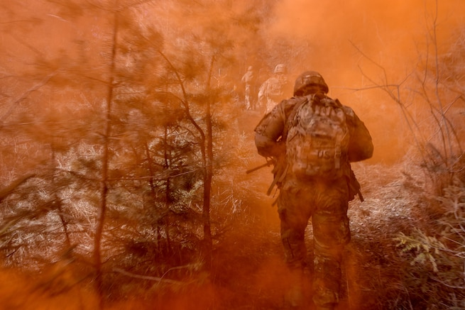 Soldiers run up a hill through orange smoke.