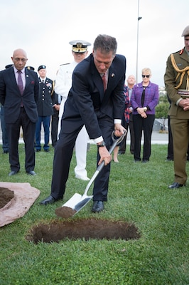 Ambassador Scott Brown covers stones from the Taranaki region of New Zealand and Pearl Harbor, Hawaii, with soil at a ceremony preparing the U.S. monument at Pukeahu National War Memorial, New Zealand for construction.