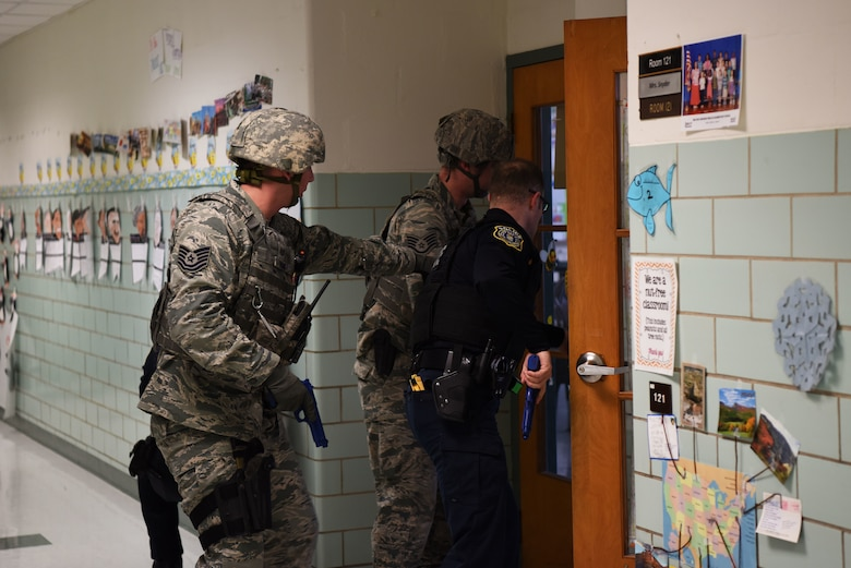 From the left, Tech. Sgt. Adam Paini, 436th Security Forces Squadron, Staff Sgt. Brandon Trapp, 436th SFS, and Officer Justin Viens, 436th SFS supervisory police officer, clear rooms during an active shooter exercise Feb. 26, 2018, at the George S. Welch Elementary School and Dover Air Force Base Middle School at Dover AFB, Del. The 436th Inspector General office evaluated school faculty and Security Forces on their response procedures. (U.S. Air Force photo by Airman 1st Class Zoe M. Wockenfuss)