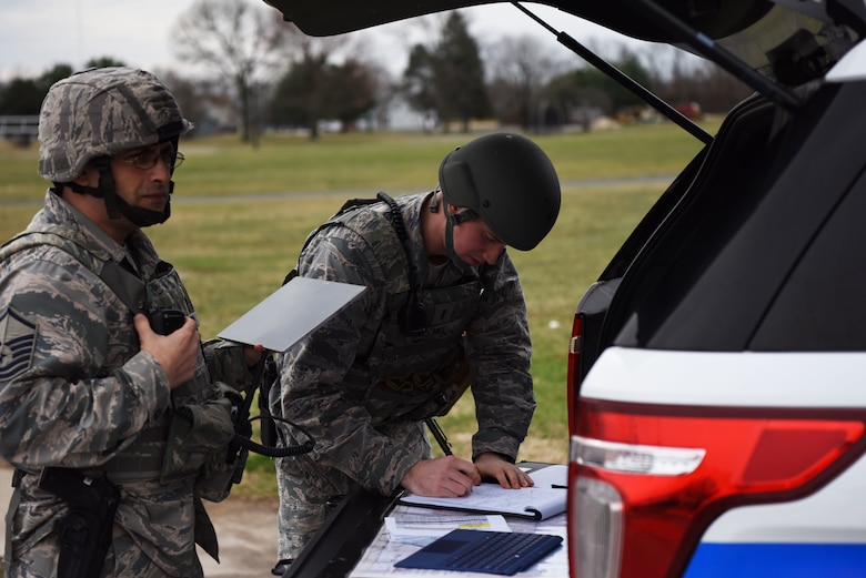 Master Sgt. Brett Snyder (left), 436th Security Forces Squadron, and 2nd Lt. Henry Hill, 436th SFS, maintain on-scene command and control of their responding forces during an active shooter exercise at the George S. Welch Elementary School and Dover Air Force Base Middle School Feb. 26, 2018, at Dover AFB, Del. A key part of the exercise was to ensure Security Forces and school faculty understood each other's roles in the event of a real world incident. (U.S. Air Force photo by Airman 1st Class Zoe M. Wockenfuss)
