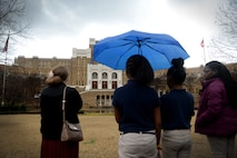 Four young ladies look at a brown building with tall white pillars. One young lady is holding a bright blue umbrella.
