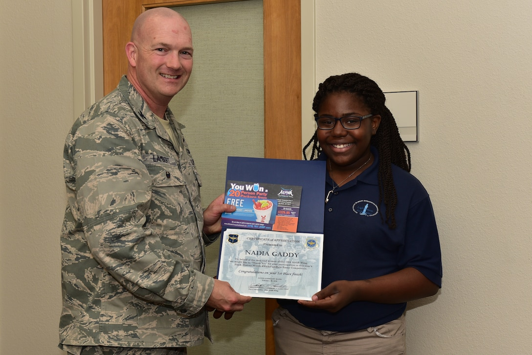 Man in the Airman Battle Uniform holds a certificate along with a young lady wearing a blue polo and glasses also holds the certificate.