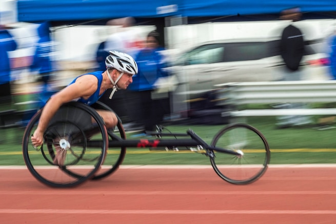 A person in a wheel chair races down a track.