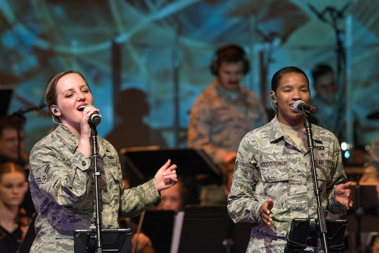 "U.S. Air Force Airman 1st Class Kayla Highsmith, left, and Senior Airman Salina Boodoosingh, both vocalists with the rock music group ""Mobility"" of The United States Air Force Band of the Golden West, Travis Air Force Base, Calif., perform with musicians from the Napa Valley Youth Symphony at the Veteran's Home in Yountville, Calif., March 4, 2018. The band and symphony are performing together after the original concert, scheduled in October 2017, was canceled due to devastating wildfires in Napa and Sonoma counties. (U.S. Air Force photo by Louis Briscese)"