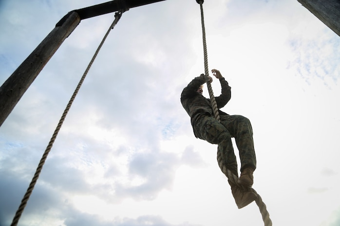 A U.S. Marine climbs the rope at the end of the obstacle course on Marine Corps Base Hawaii, March 2, 2018. In celebration of Marine Aircraft Group 24's birthday, 13 Marines from each of its subordinate units participated in the competition to develop combat readiness, competitive spirit and camaraderie. The Marines ran the course for points based on time.