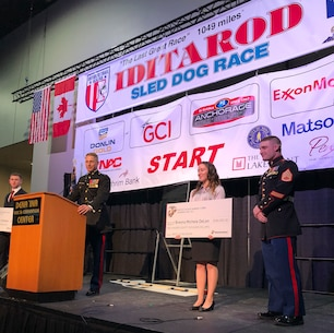 Maj. Brooks Boehlert, Commanding Officer, Recruiting Station Portland, presents two students with NROTC scholarship checks at the Iditarod Sled Dog Race Musher's Banquet in Anchorage, Alaska. The Marine Corps partnered with the Iditarod for the first time, this year, to build a long-lasting connection and to demonstrate shared values such as honor, courage and commitment. (U.S. Marine Corps Photo by Capt. Maureen Krebs/Released)