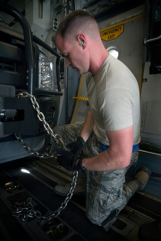 U.S. Air Force Master Sgt. Coban Goertz, a team chief assigned to the 46th Aerial Port Squadron at Dover Air Force Base, Del., anchors down a vehicle to a C-17 Globemaster III aircraft for transportation at MacDill Air Force Base, Fla., Feb. 28, 2018.