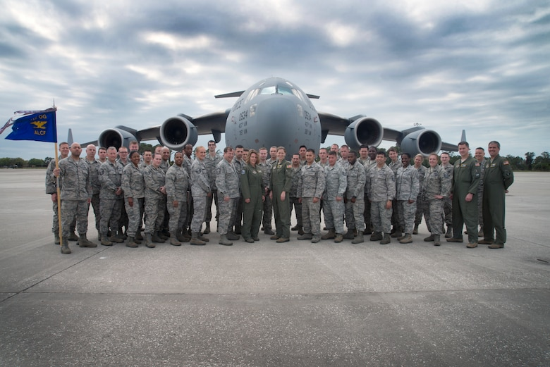 U.S. Air Force Airmen assigned to the 46th Aerial Port Squadron, 512th Contingency Response Squadron and 712th Aircraft Maintenance Squadron at Dover Air Force Base, Del., pause for a photo at MacDill Air Force Base, Fla., March 2, 2018.