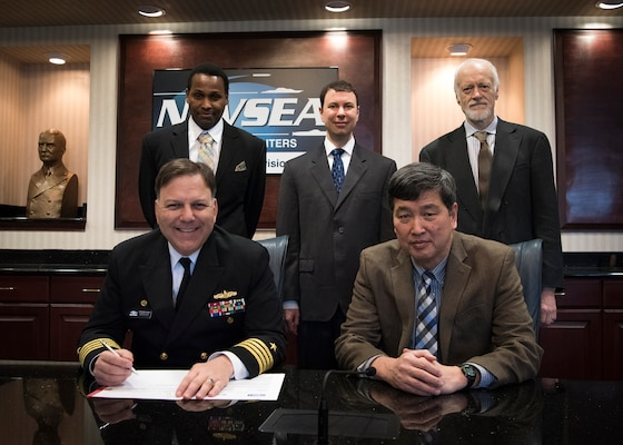 Naval Surface Warfare Center, Carderock Division Commanding Officer Capt. Mark Vandroff (left) signs an Education Partnership Agreement with the University of Iowa on Feb. 26, 2018. With its educational emphasis on naval hydrodynamics and associated technologies, the University of Iowa's partnership will seek to aid in the educational experience of students by providing staff experience and unique facilities and equipment available through Carderock. Carderock's contribution will help to encourage student interest in science, technology, engineering and mathematics. Seated next to Vandroff is Dr. Paul Shang, acting technical director for Carderock. Back row, from left is Dave Ghatt, a patent attorney in Carderock's Office of Counsel; Dr. Thad Michael, a naval architect with Carderock's Propulsors Branch; and Dr. John Barkyoumb, Carderock's director of strategic relations.