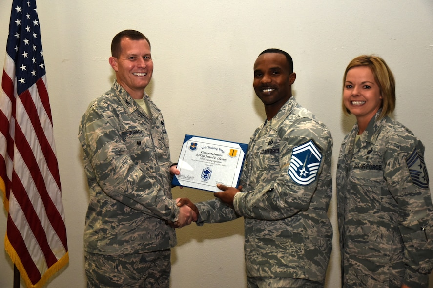 U.S. Air Force Col. Jeffrey Sorrell, 17th Training Wing vice commander, presents Master Sgt. Jamaal Chesney, 315th Training Squadron assistant first sergeant, a promotion certificate with Chief Master Sgt. Bobbie Reinsche, 17th Training Wing command chief, at the Event Center on Goodfellow Air Force Base, Texas, March 1, 2018. In celebration of individuals being selected for senior master sergeant, a party was held at the Event Center. (U.S. Air Force photo by Airman 1st Class Seraiah Hines/Released)