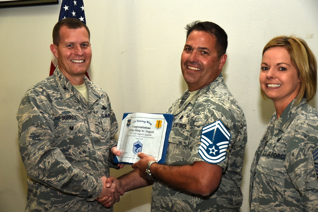U.S. Air Force Col. Jeffrey Sorrell, 17th Training Wing vice commander, presents Master Sgt. Blake Ferguson, 17th Force Support Squadron Airman Leadership School commandant, a promotion certificate with Chief Master Sgt. Bobbie Reinsche, 17th Training Wing command chief, at the Event Center on Goodfellow Air Force Base, Texas, March 1, 2018. In celebration of individuals being selected for senior master sergeant, a party was held at the Event Center. (U.S. Air Force photo by Airman 1st Class Seraiah Hines/Released)