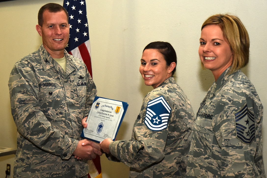U.S. Air Force Col. Jeffrey Sorrell, 17th Training Wing vice commander, presents Master Sgt. Ecatarina Garcia, 315th Training Squadron instructor, a promotion certificate with Chief Master Sgt. Bobbie Reinsche, 17th Training Wing command chief, at the Event Center on Goodfellow Air Force Base, Texas, March 1, 2018. In celebration of individuals being selected for senior master sergeant, a party was held at the Event Center. (U.S. Air Force photo by Airman 1st Class Seraiah Hines/Released)