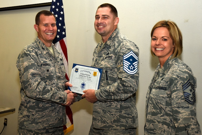 U.S. Air Force Col. Jeffrey Sorrell, 17th Training Wing vice commander, presents Master Sgt. Bryan Peel, 17th Security Forces Squadron first sergeant, a promotion certificate with Chief Master Sgt. Bobbie Reinsche, 17th Training Wing command chief, at the Event Center on Goodfellow Air Force Base, Texas, March 1, 2018. In celebration of individuals being selected for senior master sergeant, a party was held at the Event Center. (U.S. Air Force photo by Airman 1st Class Seraiah Hines/Released)