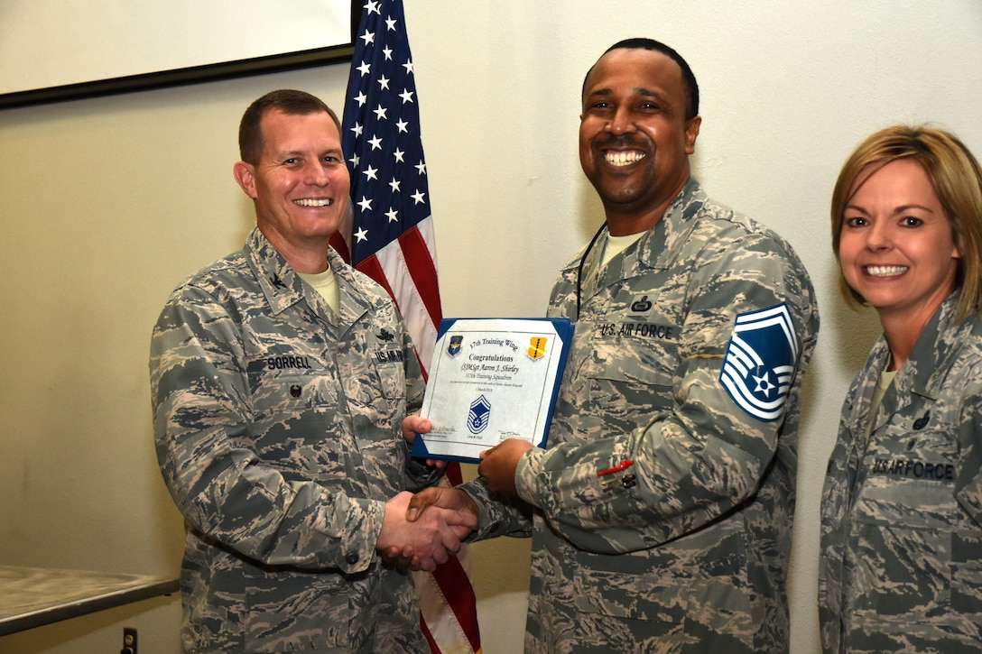 U.S. Air Force Col. Jeffrey Sorrell, 17th Training Wing vice commander, presents Master Sgt. Aaron Shirley, 315th Training Squadron instructor, a promotion certificate with Chief Master Sgt. Bobbie Reinsche, 17th Training Wing command chief, at the Event Center on Goodfellow Air Force Base, Texas, March 1, 2018. In celebration of individuals being selected for senior master sergeant, a party was held at the Event Center. (U.S. Air Force photo by Airman 1st Class Seraiah Hines/Released)