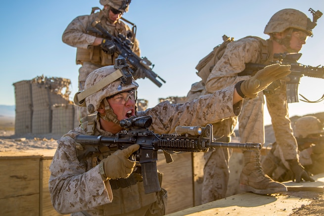 A Marine stretches out his arm and yells while other Marines move past.