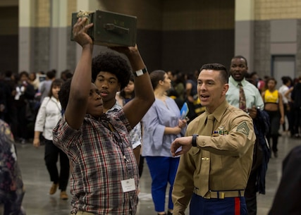 Gunnery Sergeant Bryan Davis, staff noncommissioned officer-in-charge of Recruiting Substation Charlotte, observes an attendant of the Central Intercollegiate Athletic Association (CIAA) Education Day participating in ammo-can lifts at the Charlotte Convention Center, Charlotte, North Carolina, on Feb. 28, 2018. The Marines took part in the Education Day at the CIAA to spread awareness and inform others of the opportunities the Marine Corps can provide. The Education Day assists recruiters by offering them different tools to reach students across the state. (U.S. Marine Corps photo by Lance Cpl. Jack A. E. Rigsby)