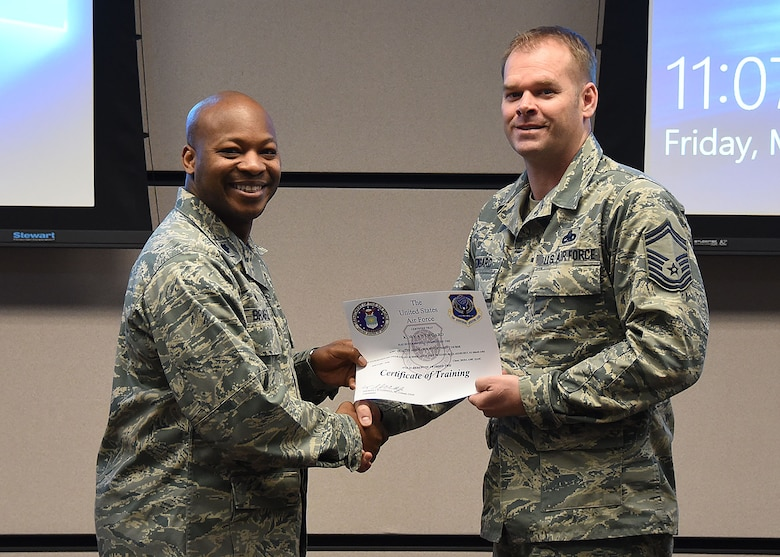 Lt. Col. Patrick Brady-Lee, 423rd Mobility Training Squadron commander, presents Senior Master Sgt. Kory Newgard, 521st Air Mobility Operations Group superintendent, a certificate of completion for the AMC Quality Assurance Supervision course, at Joint Base McGuire-Dix-Lakehurst, March 2, 2018. The course was designed to address trending deficiencies in quality assurance supervision by enhancing student's knowledge in executing the roles and responsibilities of QA superintendents and chief inspectors. (U.S. Air Force photo by Tech. Sgt. Jamie Powell)