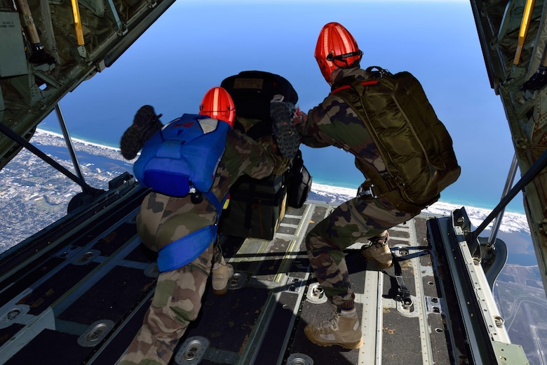 "Special Forces members jump out the back of a C-130J Super Hercules aircraft with their equipment March 2 during Emerald Warrior 2018. The 815th AS ""Flying Jennies"" from Keesler Air Force Base, Mississippi, provided airlift support for Emerald Warrior 2018, a special operations joint training event involving various units from all U.S. military branches, the U.S. Special Operations Command and North Atlantic Treaty Organization partner forces from Feb. 26 to March 9. (U.S. Air Force photo by Tech. Sgt. Ryan Labadens)"