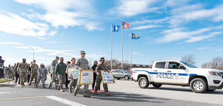 Participants in the Black History Month Unity Walk approach the main gate on their way to the base flag pole Feb. 28, 2018, on Dover Air Force Base, Del. The African-American Heritage Committee sponsored the walk here at Dover AFB and members of the 436th Security Forces Squadron provided escort and traffic control for the walk. (U.S. Air Force photo by Roland Balik)