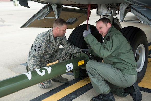 A German airman signals to a tug operator after attaching a tow bar to an Airbus A400M with the help of 167th Airlift Wing maintainer, Master Sgt. David Rinard, at the 167th AW, Feb. 23.