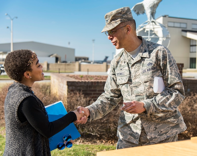 Col. Randy Boswell, 436th Mission Support Group commander, presents a coin to Ikira Peace, guest speaker for the Black History Month Unity Walk, Feb. 28, 2018, on Dover Air Force Base, Del. Peace, a native of Baltimore, Md., is a senior at the University of Delaware, Newark, Del. (U.S. Air Force photo by Roland Balik)