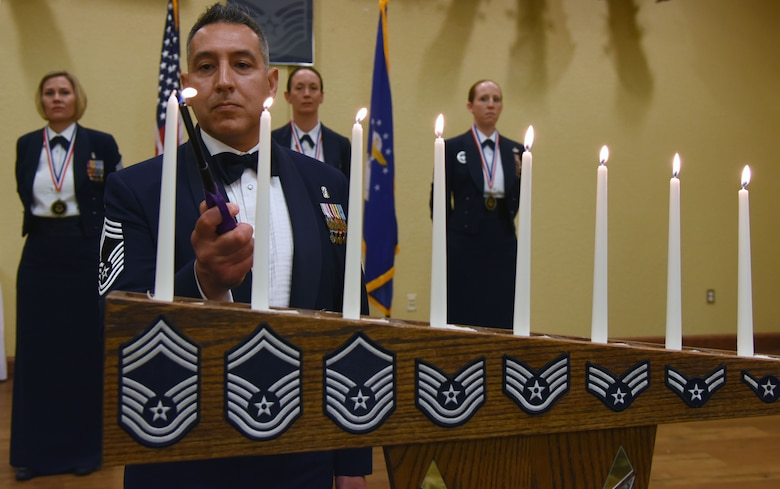 Chief Master Sgt. Claudio Castillo, 81st Surgical Operations Squadron superintendent, lights a candle during a candle lighting ceremony during the Chief Induction Ceremony at the Bay Breeze Event Center March 1, 2018, on Keesler Air Force Base, Mississippi. Three Keesler Airmen earned their chief master sergeant stripe during the 2018 promotion release. (U.S. Air Force photo by Kemberly Groue)