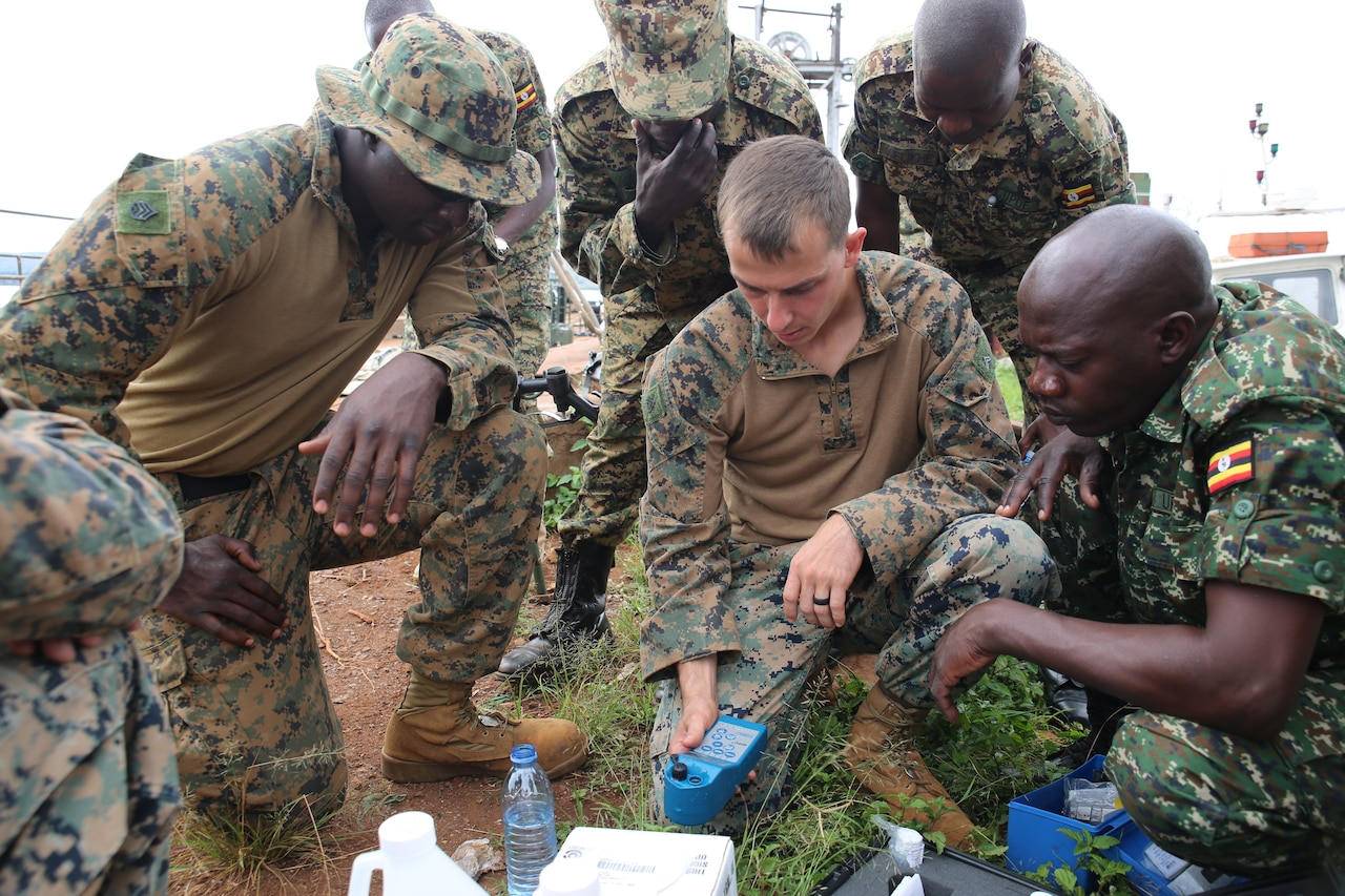 A group of Marines and Ugandan soldiers perform a water test