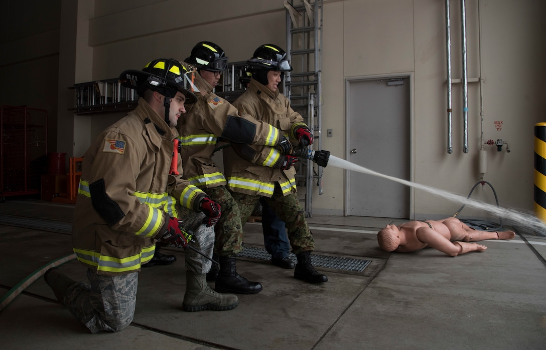 U.S. Air Force Senior Airman Daniel Brunn, left, a 35th Civil Engineer Squadron firefighter, shows Japan Ground Self-Defense Force Sergeants Kensuke Fujita, center, and Kenta Takahashi, right, how to properly handle a firehose during a JGSDF shadow program at Misawa Air Base, Japan, March 5, 2018. The program showcased Team Misawa's ability to work together with any branch of the Japan Self-Defense Force. U.S. Air Force Airmen and JGSDF Soldiers worked on their communications skills cultivating a face-to-face friendly environment for future bilateral events with the Soldiers. (U.S. Air Force photo by Senior Airman Sadie Colbert)