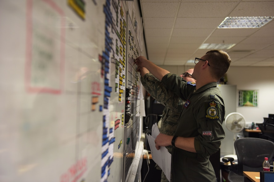 U.S. Air Force Capt. Kevin Brohaugh, 100th Operations Group assistant chief of scheduling, and Staff Sgt. Christopher Shelton, 100th Operations Group NCO-in-charge of scheduling, prepare crew schedules for a readiness exercise at RAF Mildenhall, England, Feb. 26, 2018.  The exercise tested the wing's ability to rapidly mobilize an entire wing and prepare to launch KC-135s in response to an international incident. (U.S. Air Force photo by Airmen 1st Class Alexandria Lee)