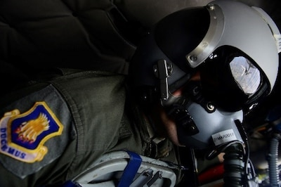 An F-18 Hornet is reflected in the face mask of an airman during a refueling operation.