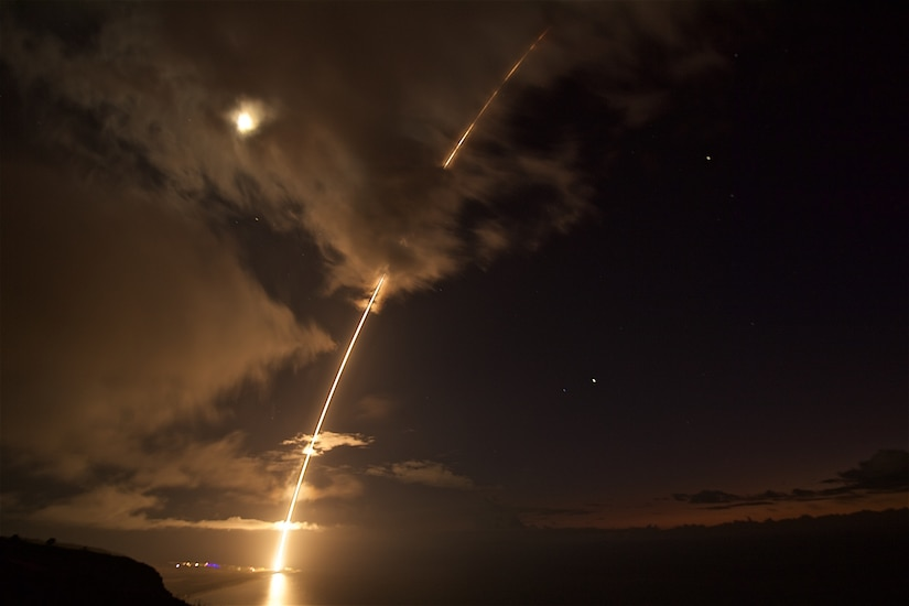 A ballistic missile target leaves a fiery arc in the night sky.