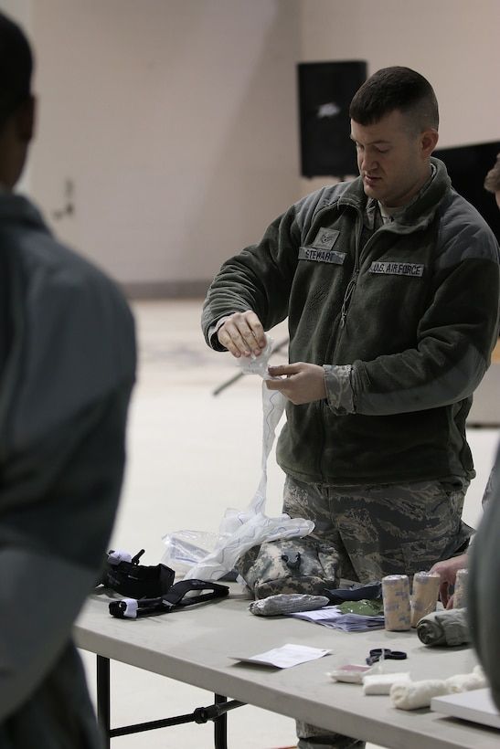 Staff Sgt. Adam Stewart, 445th Aircraft Maintenance Squadron mechanic, demonstrates how to use quick clot gauze during self-aid and buddy care training conducted during the Feb. 11, 2018 unit training assembly.