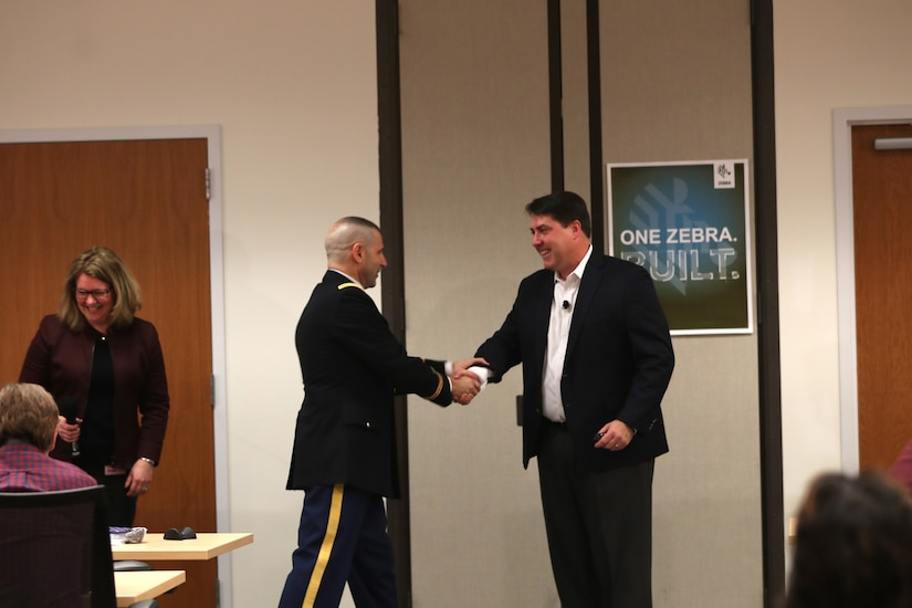 Army Reserve Col. Daniel Jaquint, left, G3 operations chief for the 85th Support Command, shakes the hand of his civilian employer, Joe White, Senior Vice President of Enterprise Mobile Computing at a company quarterly meeting in Long Island, New York, Mar. 1, 2018.