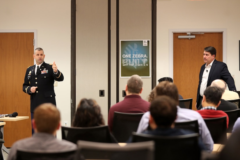 Army Reserve Col. Daniel Jaquint, left, G3 operations chief for the 85th Support Command, gives remarks about his civilian employer, Joe White, Senior Vice President of Enterprise Mobile Computing at a company quarterly meeting in Long Island, New York, Mar. 1, 2018.