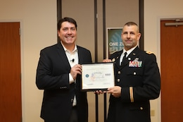 Joe White, Senior Vice President of Enterprise Mobile Computing, left, and Army Reserve Col. Daniel Jaquint, G3 operations chief for the 85th Support Command, pause for a photo after a surprise award presentation at a company quarterly meeting in Long Island, New York, Mar. 1, 2018.