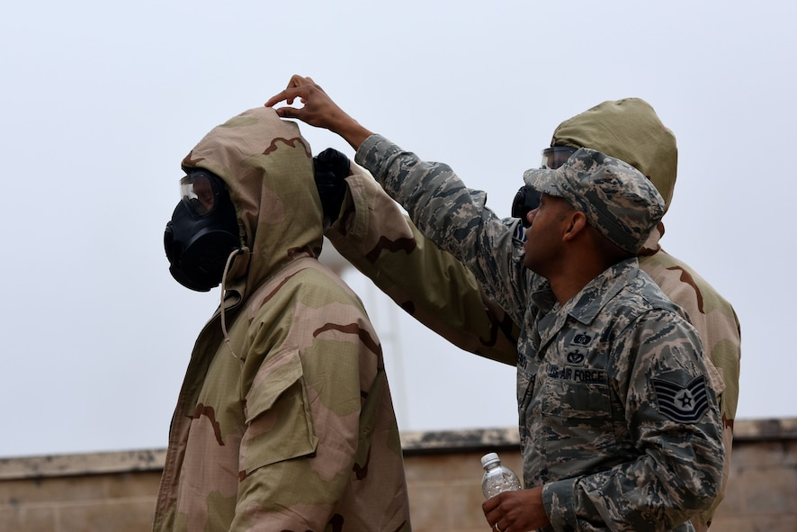 U.S. Air Force Tech. Sgt. Sheraz Cedeno, 17th Civil Engineer Squadron Chemical Biological Radiological and Nuclear instructor, demonstrates how to properly remove Mission Oriented Protective Posture gear during the final training exercise for Warrior Ancillary Specialized Training Program at the mock Forward Operating Base on Goodfellow Air Force Base, Texas, Feb. 28, 2018. The students had to perform various CBRN techniques throughout the exercise. (U.S. Air Force photo by Airman 1st Class Seraiah Hines/Released)