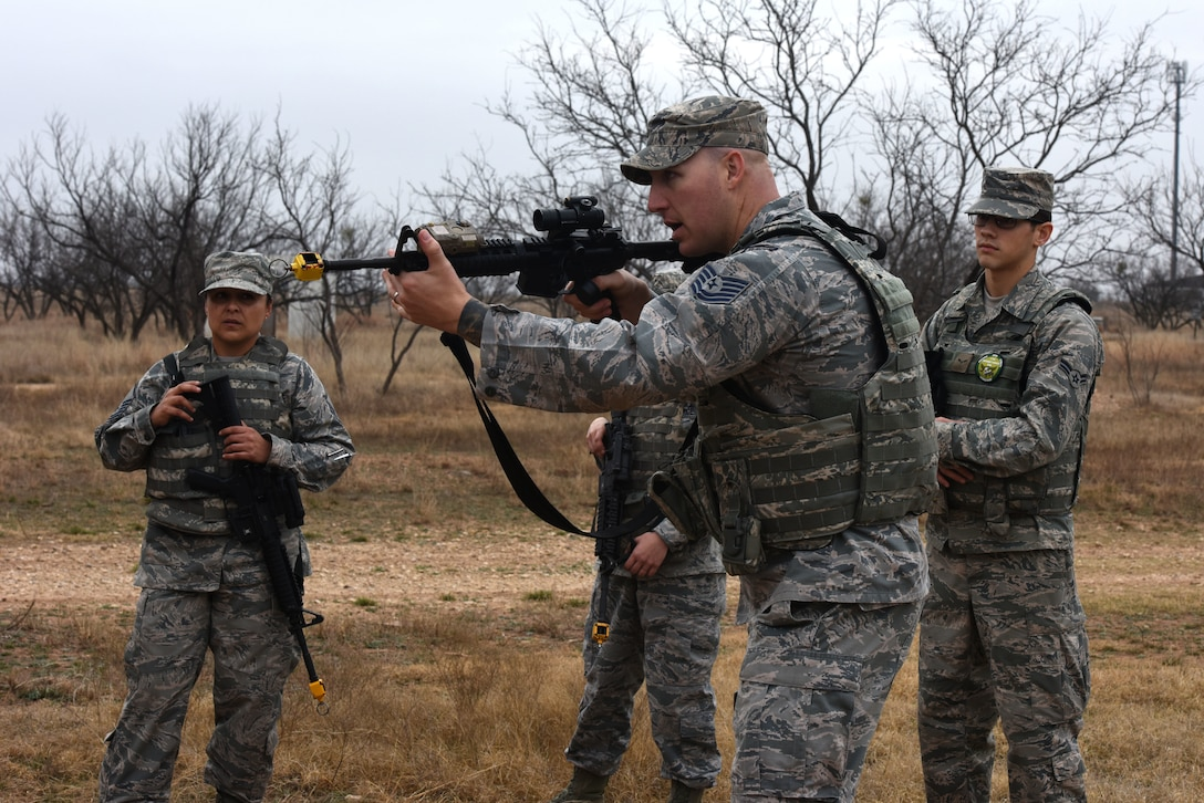 U.S. Air Force Tech Sgt. Mark Karas, 17th Security Forces Squadron noncommissioned officer in charge of training, demonstrates proper handling of a weapon during the bounding portion of exercises during the final training exercise for Warrior Ancillary Specialized Training Program at the mock Forward Operating Base on Goodfellow Air Force Base, Texas, Feb. 28, 2018. The students were taught how to take proper cover, prevent flagging, communication and other skills during the exercise. (U.S. Air Force photo by Airman 1st Class Hines/Released)
